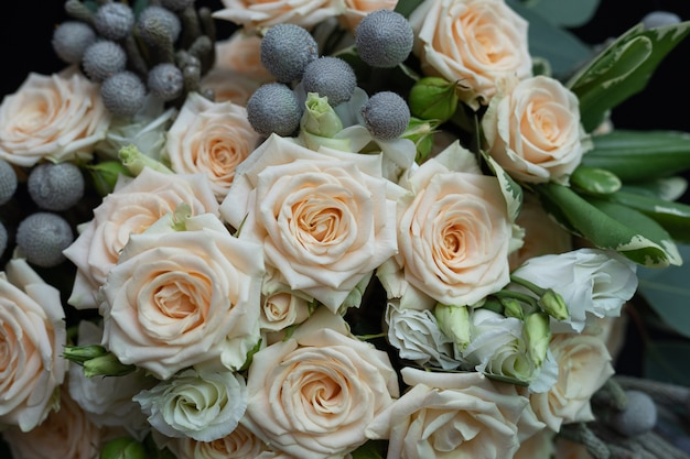 Beautiful wedding bouquet of bushy cream rose, eucalyptus, brunei, pittosporum and lisianthus on a black wall.