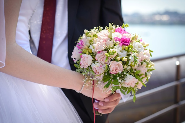 Beautiful wedding bouquet of delicate pink roses in the hands of the bride and groom close up