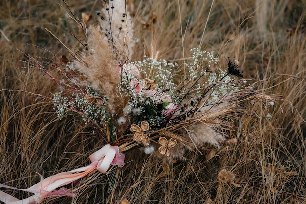 Beautiful wedding bouquet on the dry grass on an autumn day.