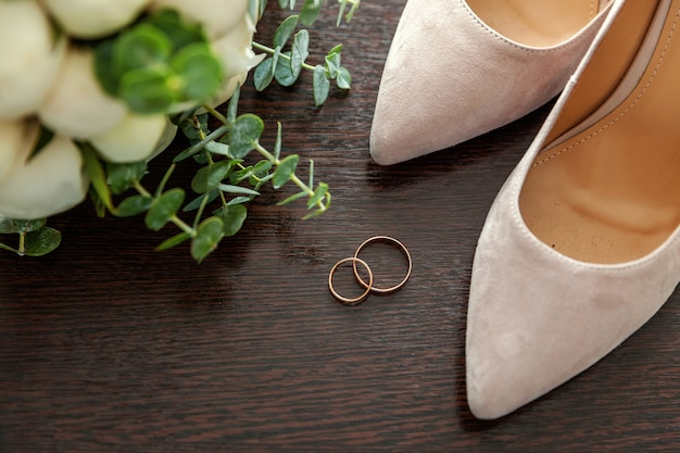 Beautiful wedding bouquet of flowers rings bridal shoes on wood