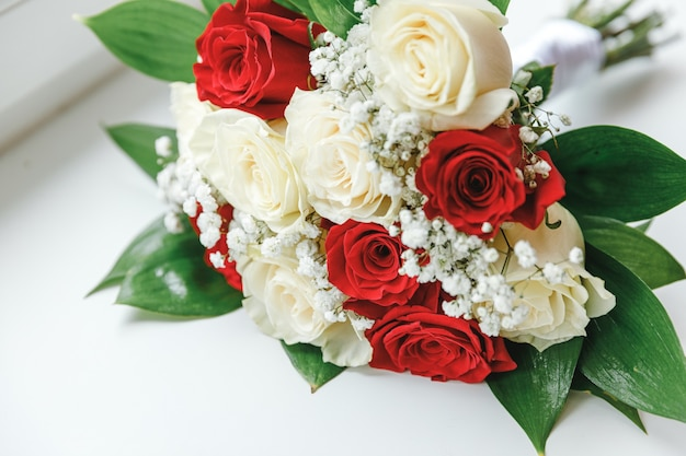 Beautiful wedding bouquet of flowers in white red colors lying on white surface background. declaration of love, spring. wedding card, valentine's day greeting. wedding day details.