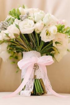 Красивый свадебный букет для невесты украшен подвеской-ключом на ручке