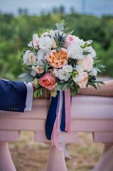 Красивый свадебный букет из роз и пионов с полосами, держась за руки на зеленом фоне. брак. вертикальный