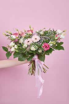 Beautiful wedding bouquet in hand on a pink background. delicate flowers