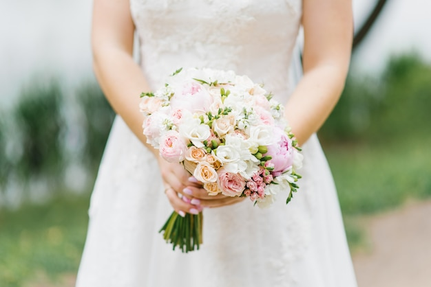 Beautiful wedding bouquet in the hands of a bride