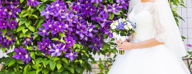 花嫁のクローズアップの手で美しいウェディングブーケ