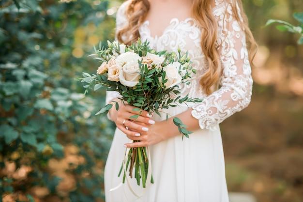 신부 손에 아름 다운 웨딩 부케입니다. 로즈, 핑크, 피치. 트렌디하고 현대적인 웨딩 꽃. 야외 웨딩 드레스 여자