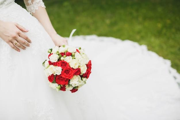 花嫁の手に美しいウェディングブーケ