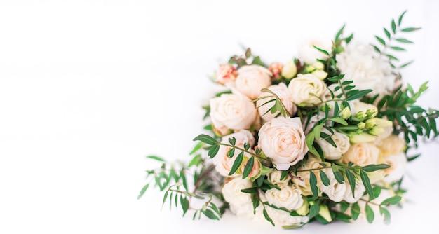 白い背景の上の明るい色の美しいウェディングブーケ。緑、白、クリーム色のバラ。テキスト用のスペース