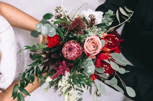 ウェディングドレスの花嫁の手に赤い色調の美しいウェディングブーケ。結婚式のアクセサリーと詳細。フラワーアレンジメント。顔が見えません。上面図。