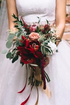 ウェディングドレスの花嫁の手に赤い色調の美しいウェディングブーケ。結婚式のアクセサリーと詳細。フラワーアレンジメント。顔が見えません。