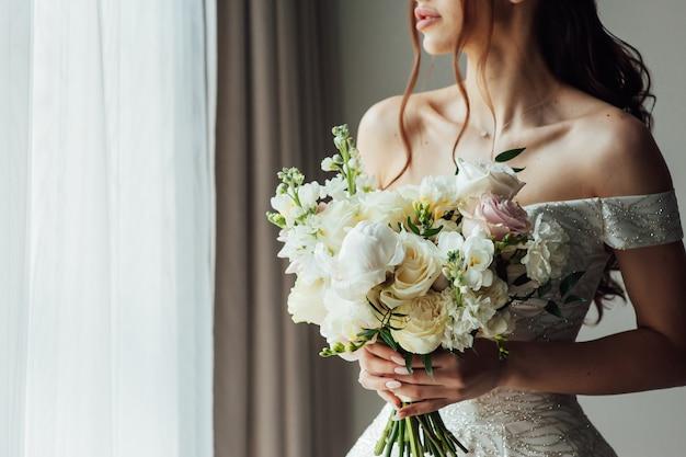 魅力的な花嫁の手に美しいウェディングブーケ。ボトックスで満たされた唇。