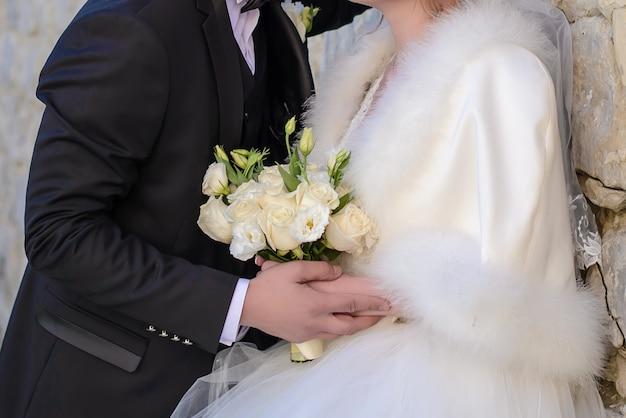 Красивый свадебный букет в руках жениха и невесты крупным планом