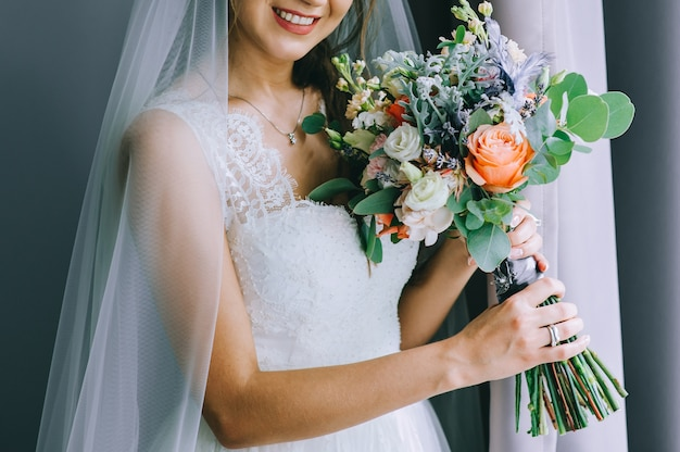 ウェディングドレスの花嫁の手に美しいウェディングブーケ。結婚式のアクセサリーと詳細。フラワーアレンジメント。