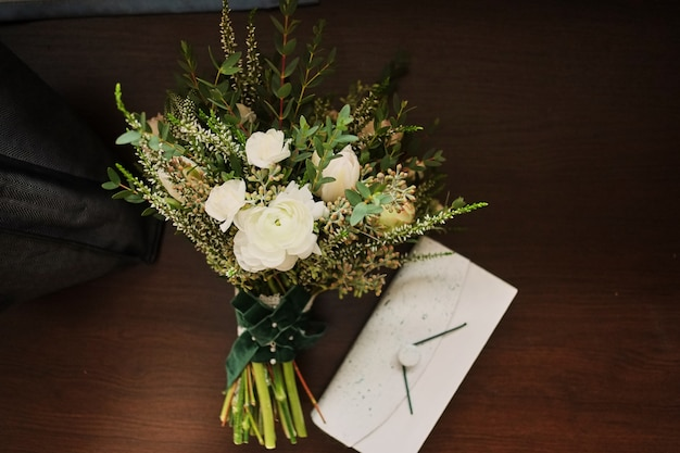 Beautiful wedding bouquet lies on a wooden background, to a white clutch