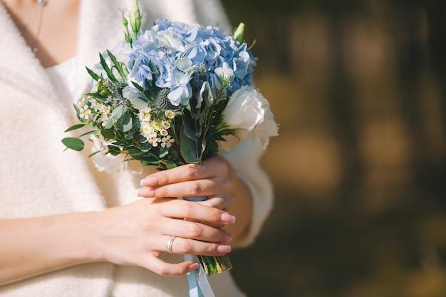 신부의 손에 꽃의 아름 다운 웨딩 부케. 복사 공간