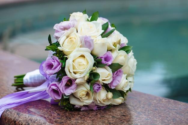 Красивый свадебный букет живых цветов на размытом фоне лежит на граните