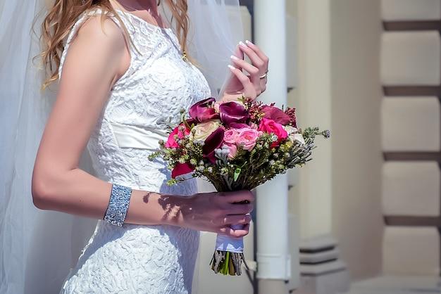 신부의 손에 분홍색과 빨간 장미의 아름다운 웨딩 부케를 닫습니다.