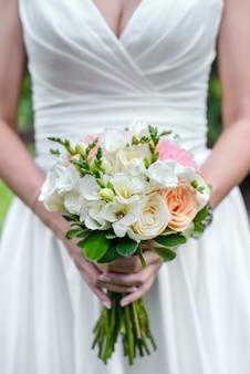 花嫁のクローズアップの手にピンクと白の花の美しいウェディングブーケ