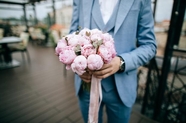 Красивый свадебный букет из розовых тюльпанов в руках жениха