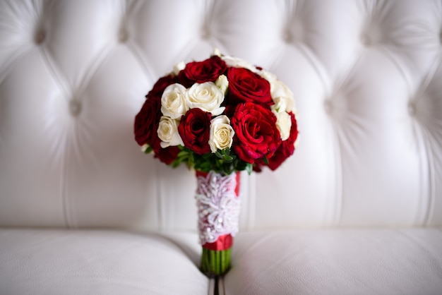 白いソファの上の赤いバラの美しいウェディングブーケ。