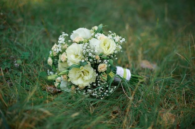 緑の草の上の白と黄色の花の美しいウェディングブーケ。屋外のスタイリッシュなブライダルブーケ