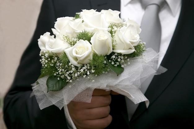 신부의 손에 흰 장미의 아름다운 웨딩 부케. 여자친구를 위한 선물