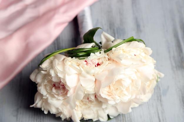 Красивый свадебный букет на цветном деревянном столе