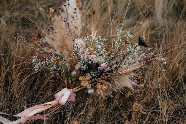 가 날에 마른 잔디에 아름 다운 웨딩 부케.