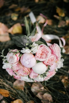 Beautiful wedding bouquet of white flowers lies on the grass