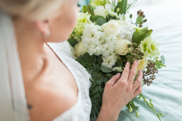 Beautiful wedding bouquet with different flowers on bride's hands.