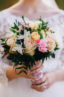 Beautiful wedding bouquet with yellow roses, white chrysanthemums and alstroemeria in hands of bride