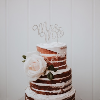 Beautiful wedding cake decorated with white roses on white wooden background