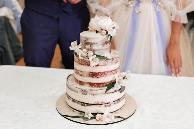 A beautiful wedding cake stands on the table next to the bride and groom
