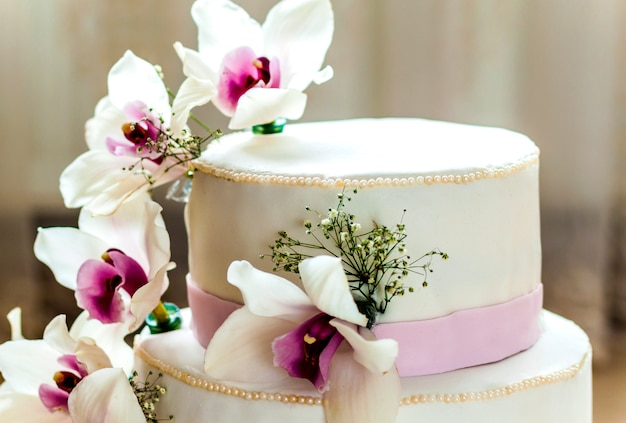 Beautiful wedding cake with flowers, close up of cake with blurr