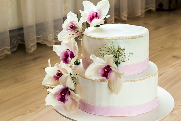Beautiful wedding cake with flowers, close up of cake with blurred