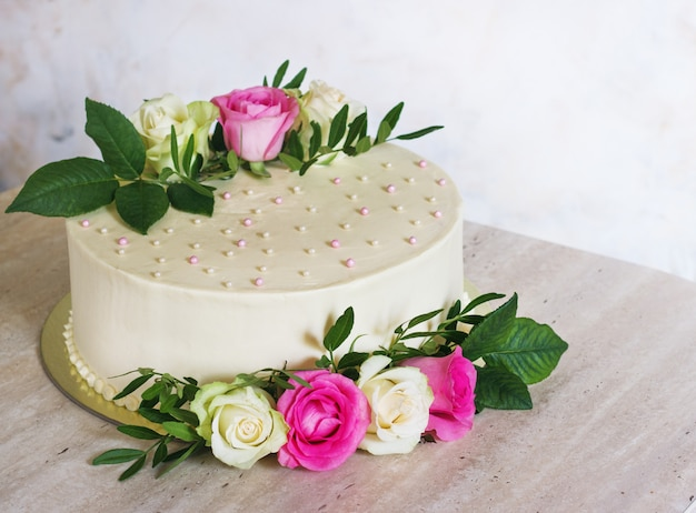 Beautiful wedding cake with flowers on marble table and white surface