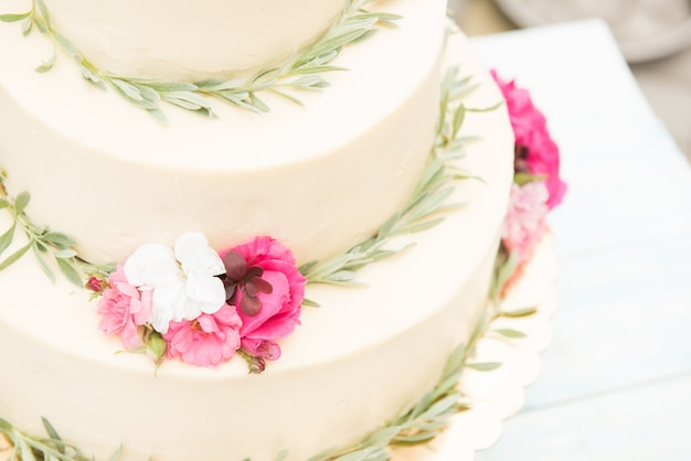Beautiful wedding cake with flowers on table