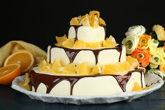 Красивый свадебный торт с апельсинами и шоколадом на темном фоне