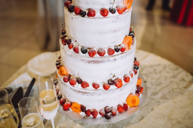 Beautiful wedding cake with red and orange fruits.