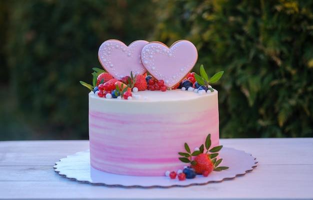신선한 딸기, 건포도 및 블루 베리로 장식 된 두 개의 하트와 아름다운 웨딩 케이크