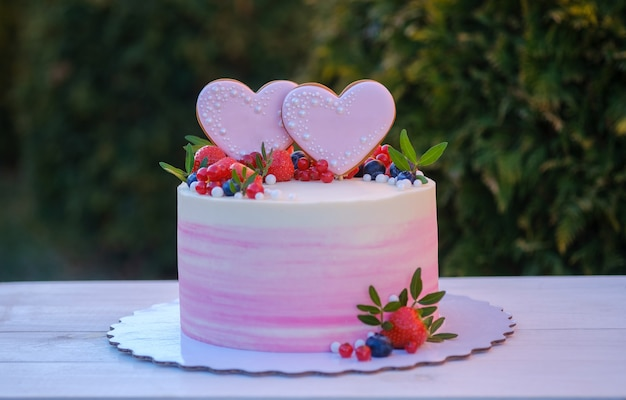 Beautiful wedding cake with two hearts decorated with fresh strawberries, currants and blueberries