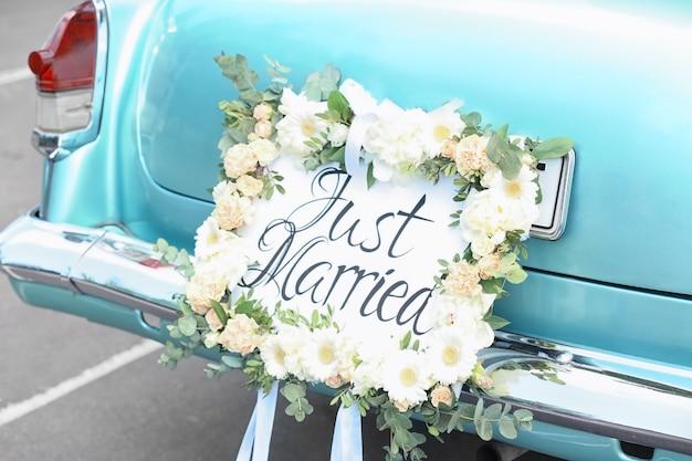 Красивая свадебная машина с табличкой just married на природе