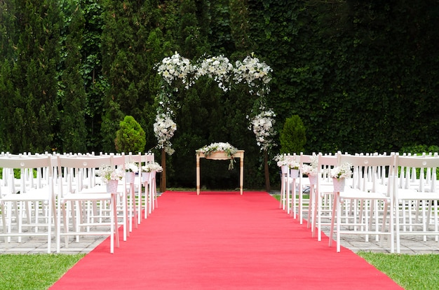 Beautiful wedding ceremony decoration, rustic altar decorated with lilies, alstroemerias and chrysanths flowers behind de ivy wall, red carpet with whites chairs. wedding day concept.