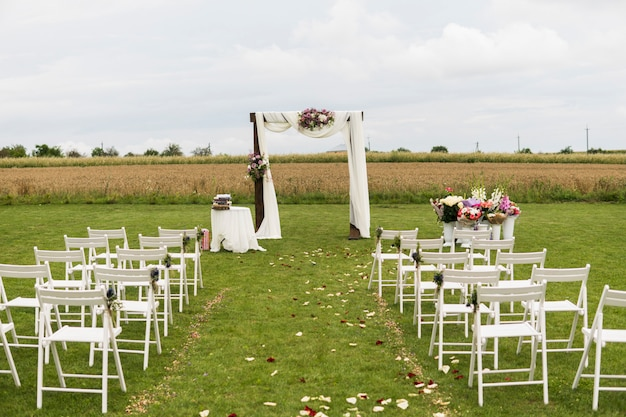 Beautiful wedding ceremony on a field with white chairs. place for wedding ceremony with wedding arch decorated with cloth, flowers and white chairs on each side of archway outdoors.