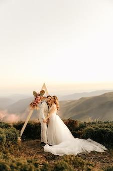 Красивая свадебная церемония в горах, влюбленная свадебная пара держится за руки и улыбается.