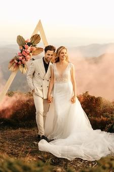 Красивая свадебная церемония в горах, свадебная пара влюбленных молодоженов, объятия и улыбки, свадьба на природе.