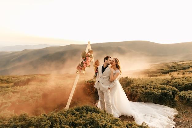 산에서의 아름다운 결혼식, 사랑의 포옹과 미소에 신혼 부부의 웨딩 커플, 자연에서의 결혼식.