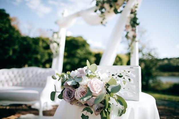 호수 기슭의 아름다운 결혼식과 신선한 꽃이있는 아치