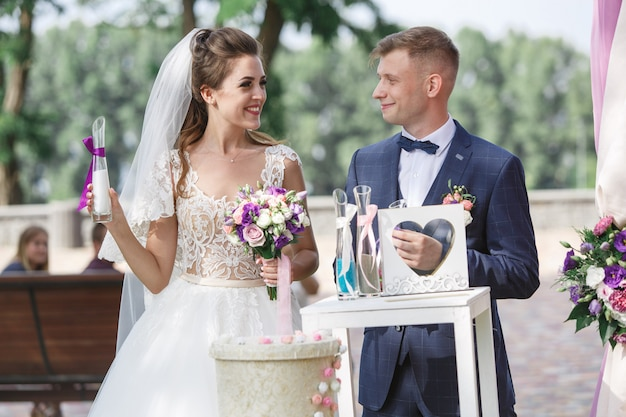 Beautiful wedding ceremony outdoors in sunny day. happy bride and groom  exchange with wedding rings.